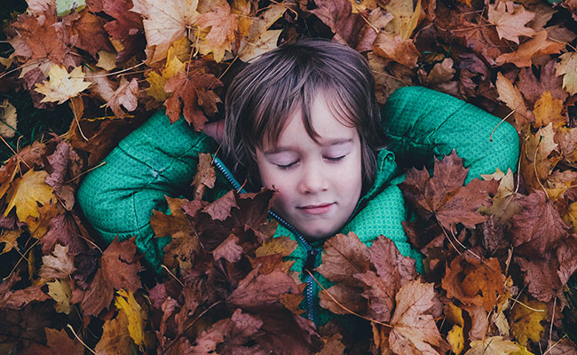 Small child in autumn leaf pile eyes closed smiling