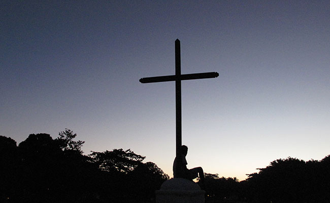 Woman sitting at the base of the cross