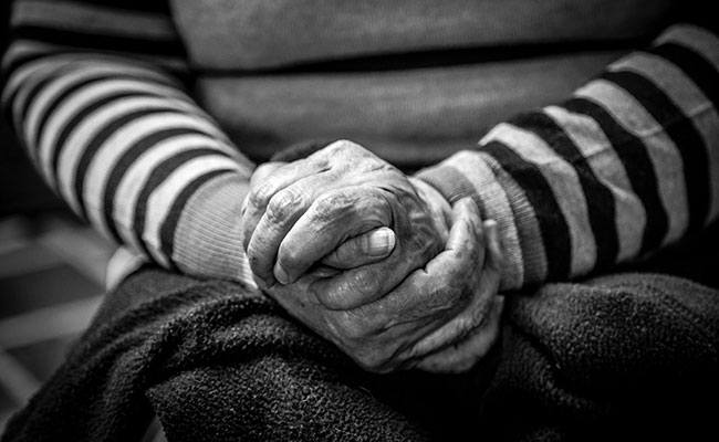 An old woman clasping her hands