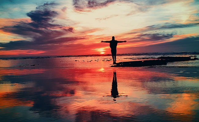Man with raised arms looking into the sunset