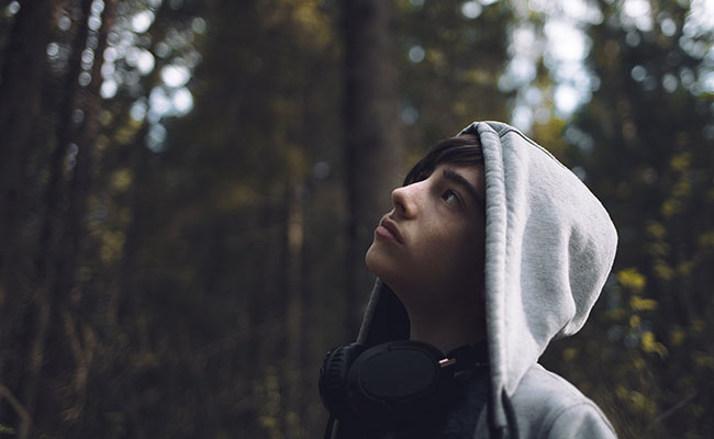 Young teen boy looking up