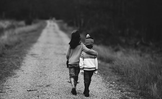 Two children walking one with arm around the other