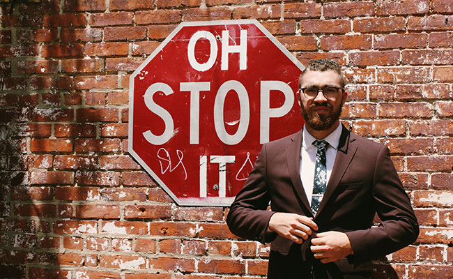 Man beside Oh Stop It sign